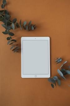 Tablette écran blanc avec branche d'eucalyptus sur orange foncé