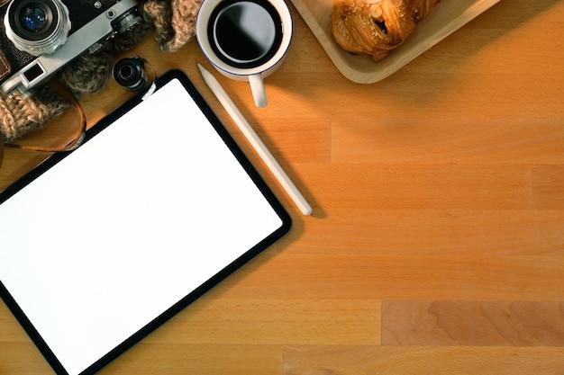 Tablette écran blanc sur un bureau élégant en bois avec fournitures de photographe créatif