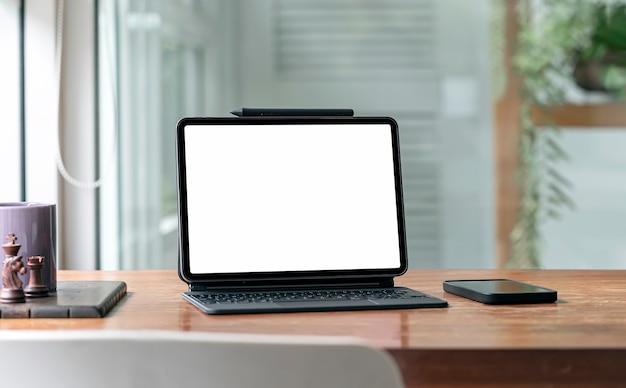 Tablette à écran blanc avec clavier magique et smartphone sur table en bois dans le salon.
