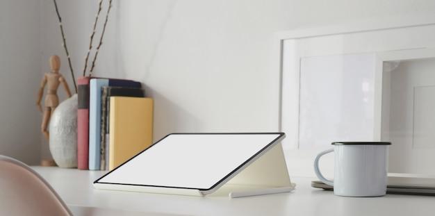 Tablette écran blanc dans l'espace de travail minimal blanc avec fournitures de bureau