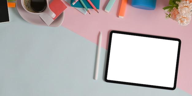Une tablette à écran blanc et divers équipements mettent sur une table à deux tons