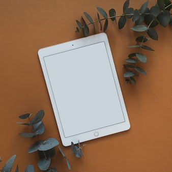 Tablette écran blanc avec espace copie vide, branche d'eucalyptus sec sur rouge foncé