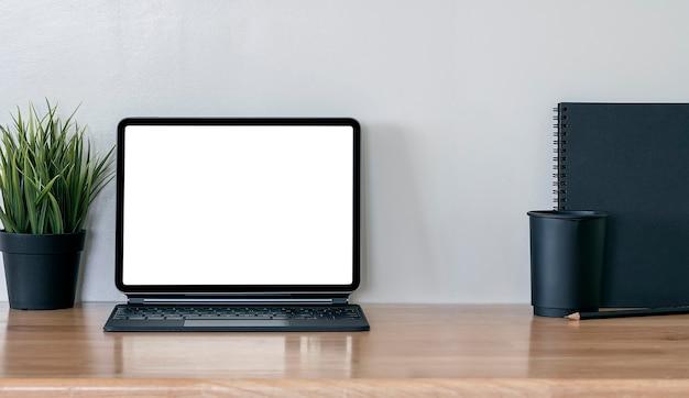 Tablette écran blanc maquette avec clavier sur table en bois.