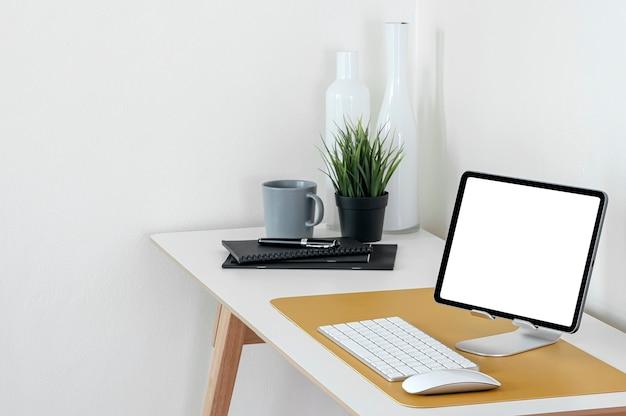 Tablette écran blanc maquette avec fournitures sur table en bois dans la salle blanche.