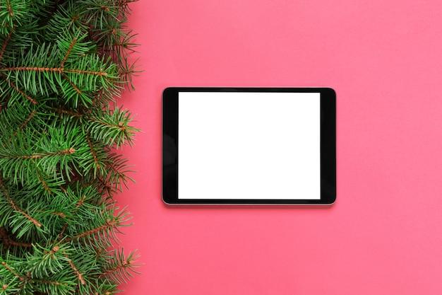 Tablette avec un écran blanc sur le pastel rose