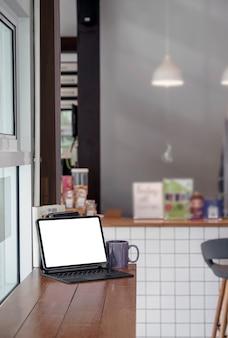 Tablette à écran blanc vierge avec clavier magique sur table de comptoir en bois dans la salle de café, vue verticale.