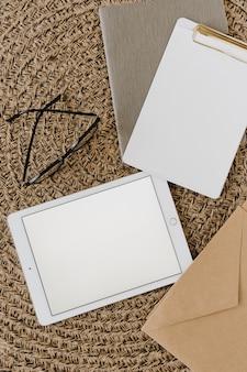 Tablette avec écran de l'espace de copie de maquette vierge, presse-papiers, enveloppe sur fond de rotin