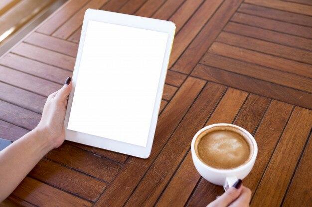 Tablette avec écran isolé à la main dans un café