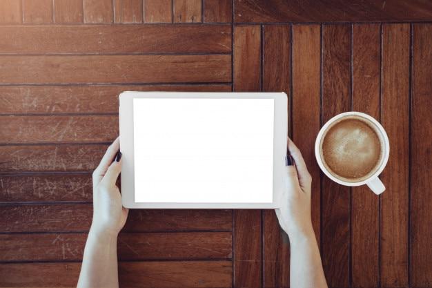 Tablette avec écran isolé à la main sur la table en bois dans le café