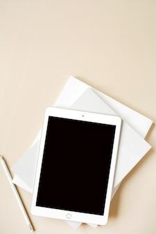 Tablette avec écran tactile blanc sur beige neutre. mise à plat, vue de dessus. freelance, blogueur, espace de travail minimaliste pour le bureau à domicile