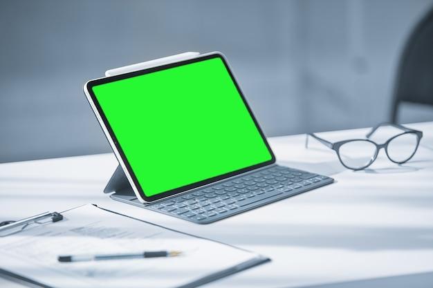 Une tablette avec un écran vert sur un bureau blanc au bureau, à côté des lunettes et un stylo