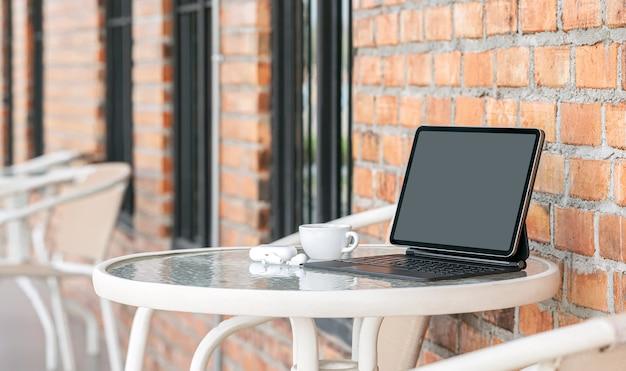 Tablette à écran vierge maquette avec clavier sur la table à l'extérieur de la salle du café.