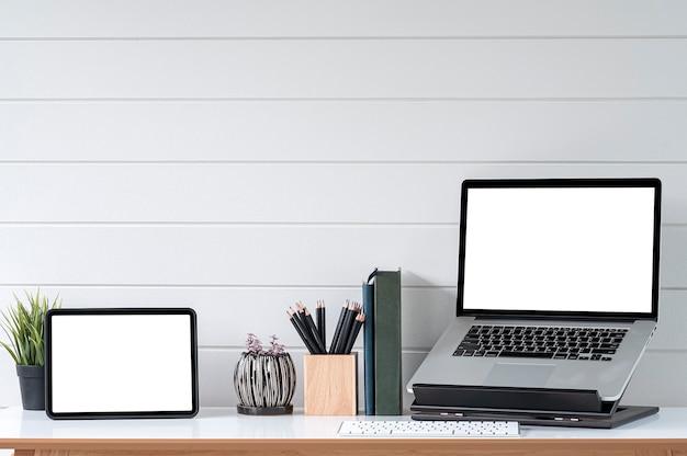 Tablette à écran vierge et ordinateur portable dans une salle de bureau minimale avec décorations et espace de copie.