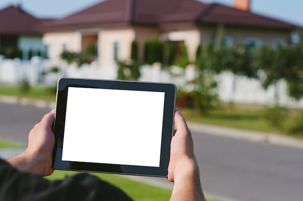 Une tablette entre les mains d'un homme, sur fond de maison.