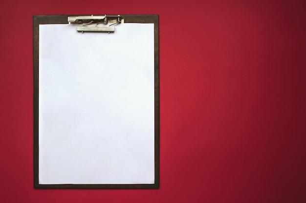 Tablette avec une feuille de papier se trouve sur le fond rouge. modèle de maquette pour les présentations. concept de bureau à domicile.