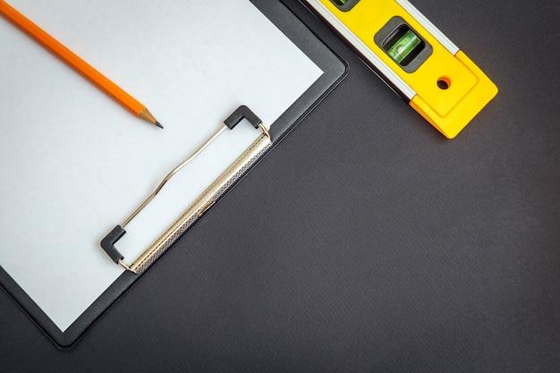 Tablette avec feuille de papier vierge pour l'élaboration d'un plan de travail et niveau bâtiment