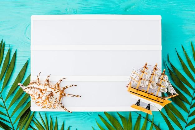 Tablette avec des feuilles de plantes près de bateau jouet et coquillage
