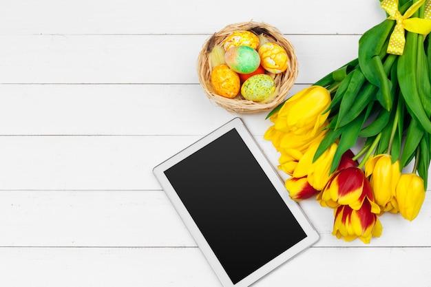 Tablette, fleurs de tulipes colorées et oeuf de pâques