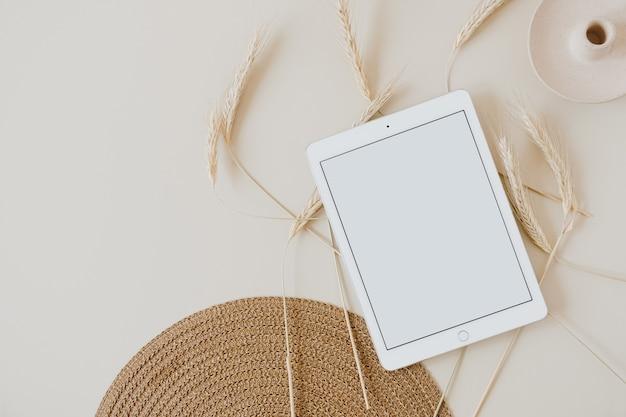 Tablette sur fond beige avec tiges de seigle de blé et serviette en osier. mise à plat, vue de dessus.