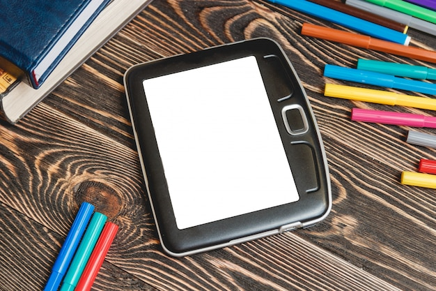 Tablette et fournitures scolaires sur fond en bois