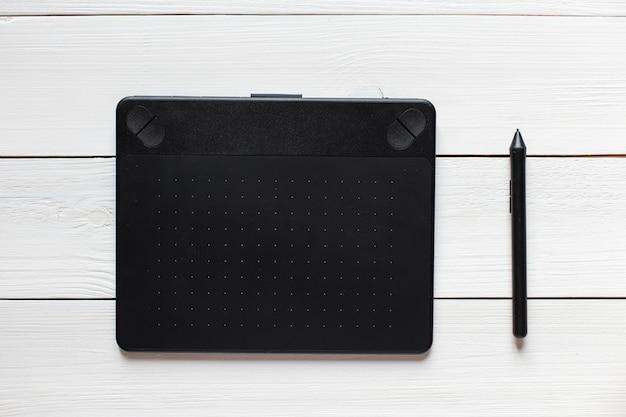 Tablette graphique noire sur le bureau blanc