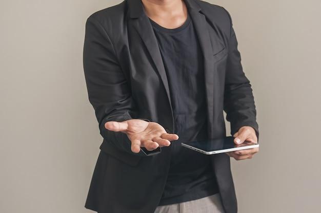 Tablette holding homme d'affaires de la poignée de main sur fond de mur gris