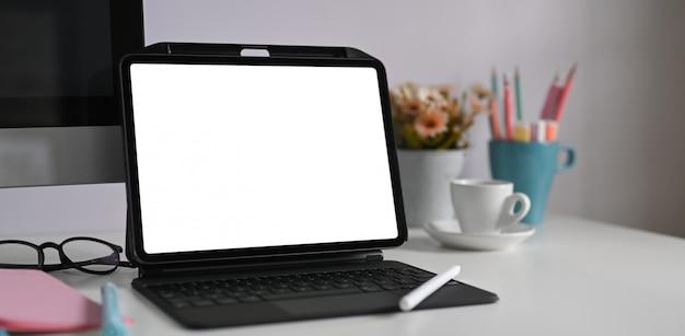 Une tablette informatique avec un étui à clavier met sur un bureau blanc entouré de divers équipements