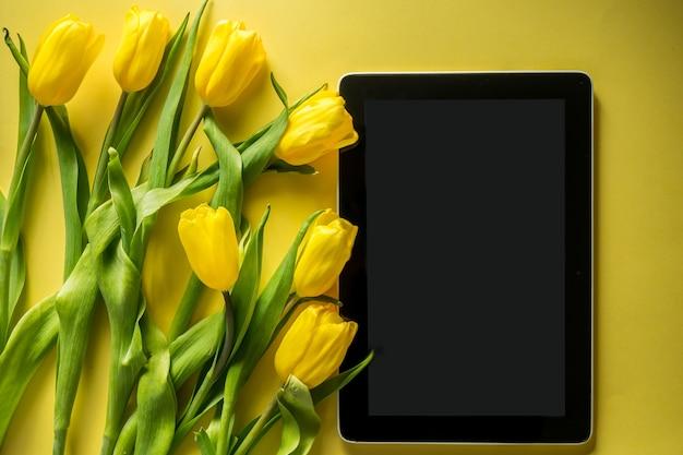 Tablette informatique maquette avec bouquet de tulipes sur la vue de dessus sur fond jaune coloré photo panoramique