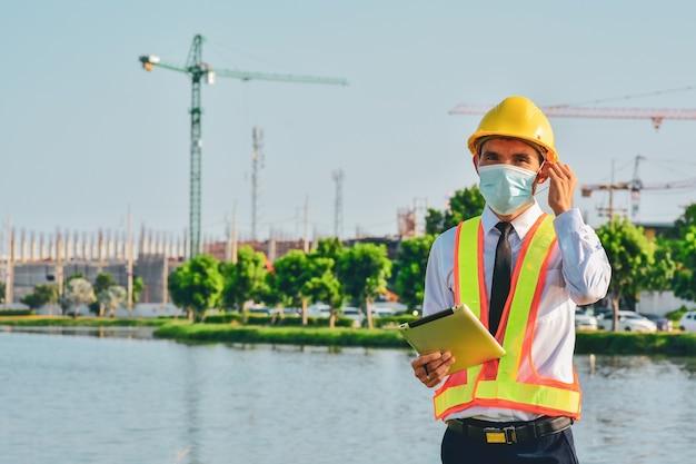 La tablette de l'ingénieur d'architecture travaille dur la construction du site, la fête du travail