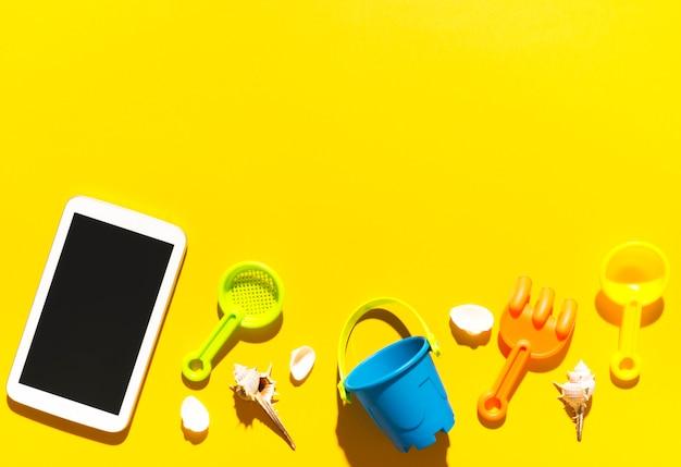Tablette et jouets de plage sur une surface colorée