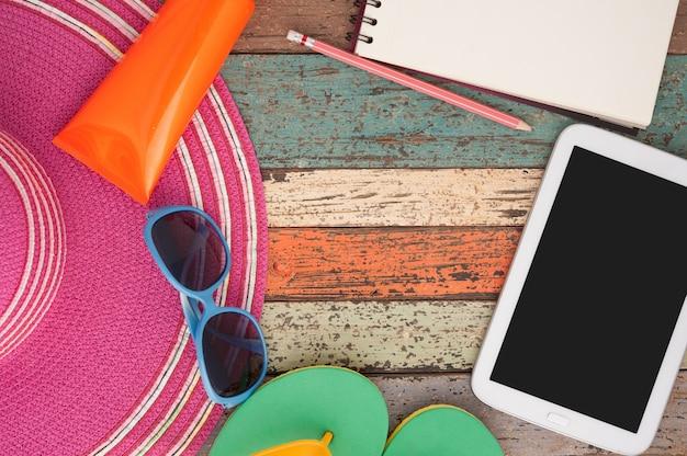 Tablette et lunettes de soleil en paille sur bois vintage.