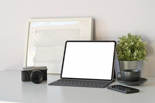 Tablette de maquette de bureau à domicile avec un clavier intelligent sur une table de travail blanche minimale.
