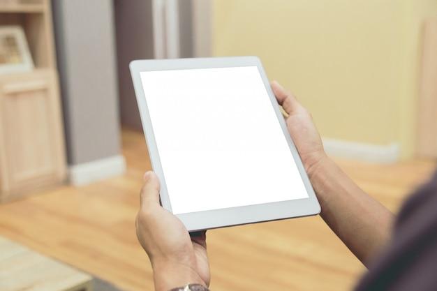 Tablette de maquette sur les mains de l'homme d'affaires affiche vide sur la table de la maison