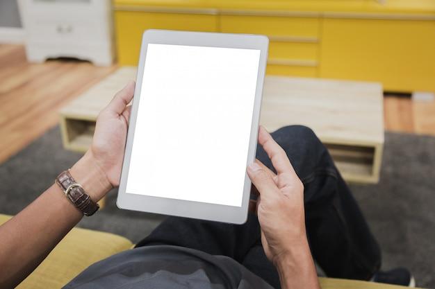 Tablette de maquette sur les mains de l'homme d'affaires affichent vide sur la table de la maison.