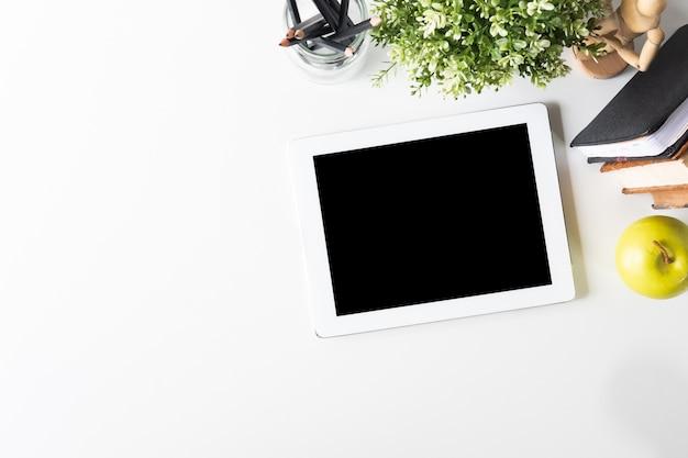 Tablette de maquette numérique sur l'espace de travail avec table de vue supérieure.