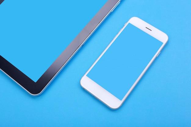 Tablette de maquette vue de dessus et smartphone sur fond bleu pastel