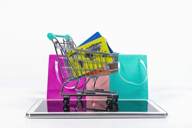 Tablette, mini panier avec cartes de crédit et sacs en papier colorés isolés sur blanc, commerce électronique