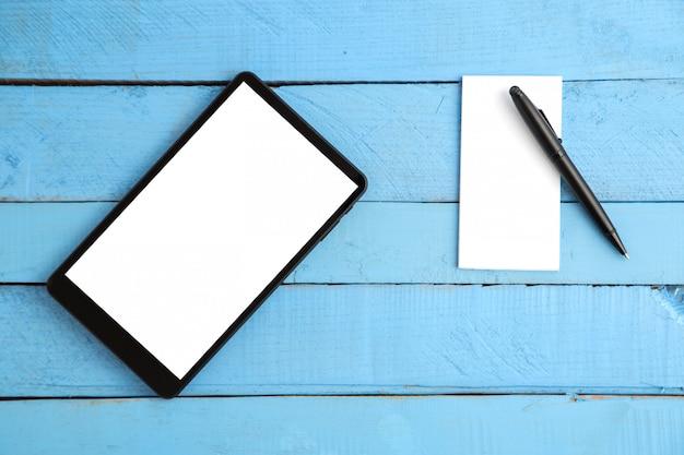 Tablette noire, petit carnet et stylo noir sur bois bleu
