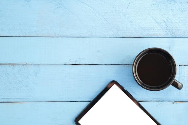 Tablette noire et une tasse de boisson sur un bois bleu