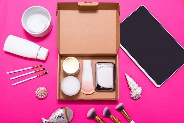 Tablette numérique et boîtes d'abonnement de maquillage sur table rose, vue de dessus, flatlay