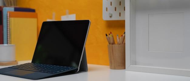 Tablette numérique sur un bureau de bureau à domicile créatif avec papeterie, cadre et livres