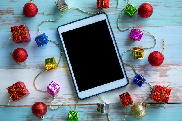 Tablette numérique et coffret cadeau sur fond en bois. vue d'en-haut