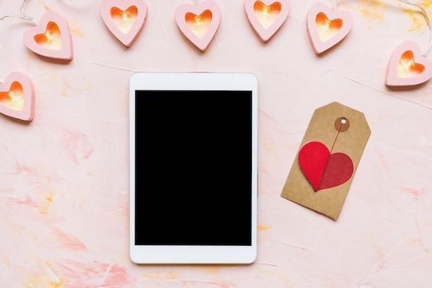 Tablette numérique, décoration de coeurs rouges et étiquette d'étiquette sur le bureau. préparation de la saint-valentin, shopping