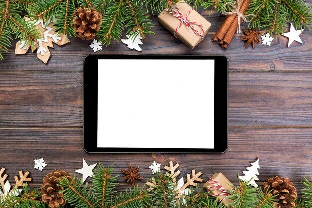 Tablette numérique avec décorations de noël rustiques pour la présentation de l'application. vue de dessus