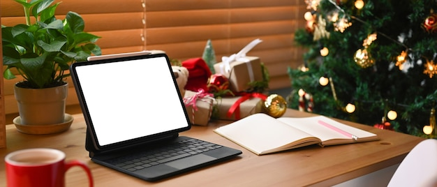 Tablette numérique avec écran blanc et coffrets cadeaux de noël sur table en bois.