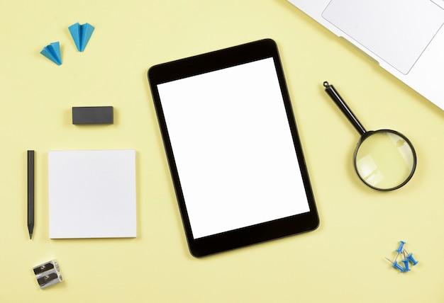 Tablette numérique écran blanc avec des fournitures de bureau sur fond jaune