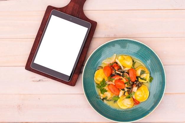 Tablette numérique d'écran blanc sur une planche à découper et de délicieuses pâtes de raviolis dans une assiette sur une table en bois