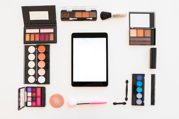 Tablette numérique à écran blanc avec des produits de beauté pour un maquillage professionnel sur fond blanc