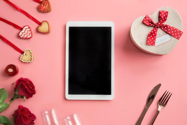 Tablette numérique avec écran blanc, roses, coeurs et coffret cadeau. vue de dessus.