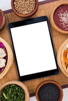 Tablette numérique avec écran vierge blanc entouré de bateaux à vapeur; graines de coriandre; graines de sésame et oignons de printemps sur napperon